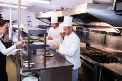 Group of chef preparing food in commercial kitchen Stock Images