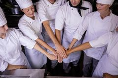 Group of chefs formig hands stack in kitchen royalty free stock photography