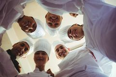 Group of chefs formig huddles in kitchen royalty free stock photo