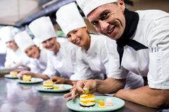 Group of chefs garnishing delicious desserts in a plate royalty free stock photography