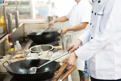 Group of chefs in hotel or restaurant kitchen busy cooking.  Royalty Free Stock Photo