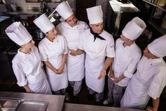 Group of chefs interacting wiht each other in kitchen royalty free stock image