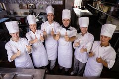 Group of chefs showing thumbs up sign in kitchen stock photo