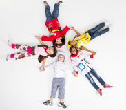 Group of children. Group of cute little children in various workers uniforms lying on floor stock photos