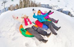 Group of children with arms up slide on tubes. Happy group of children with arms up sliding down on the tubes together during beautiful winter day with trees Stock Photos