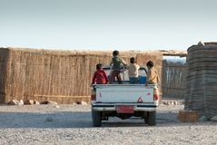 A group of children in the back of a pickup truck ride through a Bedouin village in Sinai Peninsula stock photo