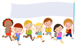 Group of children with bags and holding banner Stock Photo