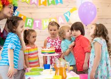 Cute little kid congratulating friend birthday boy. Group of children at birthday party. Cute little kid congratulating friend birthday boy stock photography