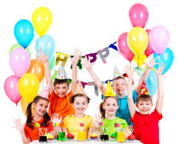 Group of children at the birthday party with raised hands. Royalty Free Stock Photo