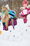 Group of children builds wall from snow blocks Royalty Free Stock Images