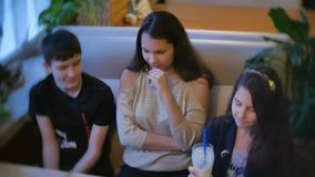 Group of children in a cafe are eating milkshakes. teenagers kids children in cafes slow motion video fun joy. Group of children in cafe are eating milkshakes stock video