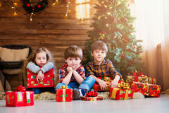 Group children with Christmas presents. Dreamers. Background Christmas tree Stock Photo