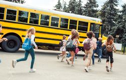 Classmates running to school bus back view late
