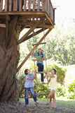 Group Of Children Climbing Rope Ladder To Treehouse Stock Photography