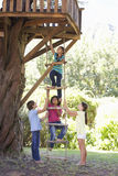 Group Of Children Climbing Rope Ladder To Treehouse Royalty Free Stock Photo