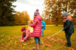 Group of children collecting leaves in autumn park Stock Photos
