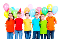 Group of children in colored t-shirts and party hats. Stock Image