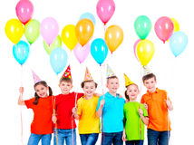 Group of children in colored t-shirts and party hats. Royalty Free Stock Photo