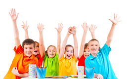 Group of children in colored t-shirts with raised hands. Group of children in colored t-shirts sitting at a table with raised hands Royalty Free Stock Image