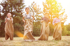 Group of children competing at sack race. Interracial group of children competing in a sack race at the park Stock Photography
