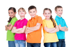 Group of children with crossed arms. Group of smiling children with crossed arms in colorful t-shirts standing together on white background Stock Image
