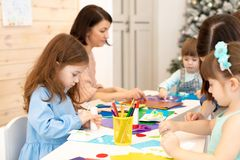 Group of children at daycare. Preschool children working with color paper, sciccors and glue on art class in royalty free stock image