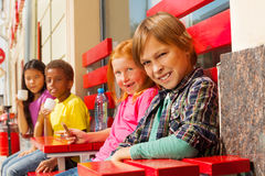 Group of children diversity sit outside in cafe. Group of children diversity sitting outside in summer on red wooden benches and tables in cafe and drinking Stock Photos