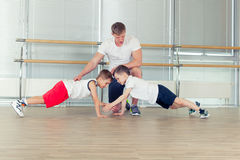 Group of children doing kids gymnastics in gym with nursery teacher Royalty Free Stock Photography