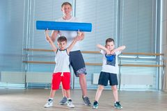 Group of children doing kids gymnastics in gym with teacher. Happy sporty children in gym. foam roller Stock Photography
