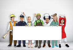Group of Children in Dreams Job Uniform Holding Banner with Copy Royalty Free Stock Image
