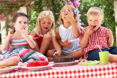 Group Of Children Eating Cake At Outdoor Tea Party Royalty Free Stock Photography