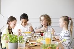 Group of children eating healthy dinner royalty free stock photography