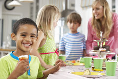 Group Of Children Enjoying Birthday Party Food At Table Stock Image
