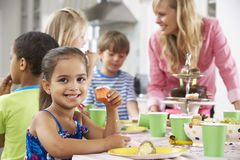 Group Of Children Enjoying Birthday Party Food At Table Royalty Free Stock Photography