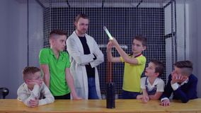 Group of children explores Tesla coil using electric lamp over the it. Children and laboratory assistant make physical experiment with Tesla coil in scinetific stock video