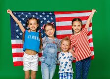 Group of children with flag of   United States of America USA on green   background. Group of children with flag of the United States of America USA on green royalty free stock photos