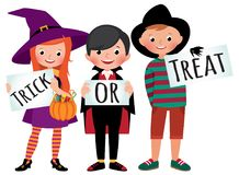 Group of children in Halloween party costumes hold a board Stock Photo