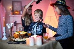 Group of Children Having Fun at Halloween Party. Portrait of children wearing Halloween costumes playing in decorated room during party, standing by table with Stock Photo