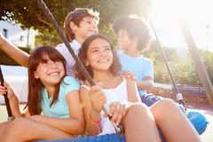 Group Of Children Having Fun On Swing In Playground Stock Photo