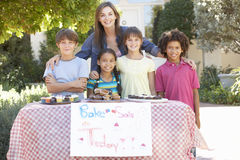 Group Of Children Holding Bake Sale With Mother Stock Images