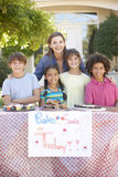Group Of Children Holding Bake Sale With Mother Royalty Free Stock Image