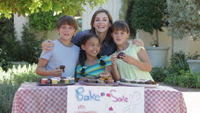 Group Of Children Holding Bake Sale With Mother stock video