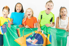 Group of children holding a Brazil flag. And international flags. Rio de Janeiro at Brazil. Happy fans of kids watching tv. Multiracial people. Volunteer stock image