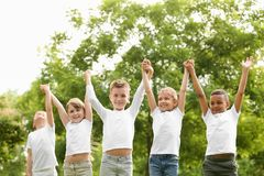 Group of children holding hands up. Volunteer project stock image