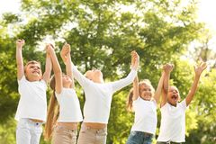Group of children holding hands up in park stock image