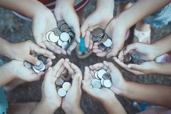 Group of children holding money in hands in the circle together. As finance and charity concept Stock Image