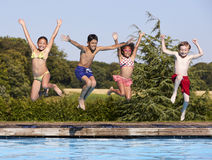 Group Of Children Jumping Into Outdoor Swimming Pool Royalty Free Stock Photo