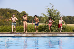 Group Of Children Jumping Into Outdoor Swimming Pool Royalty Free Stock Photography