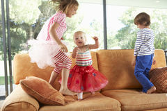 Group Of Children Jumping On Sofa Stock Photos