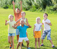 Group of children  jumping together on green grass in park Stock Photo
